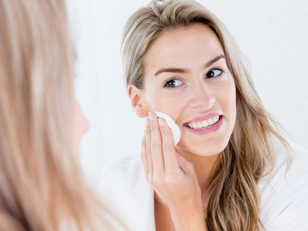 Woman applying skin cleanser to help with acne prevention